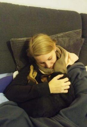 egy lány és a kiskutyája összebújnak az ágyban